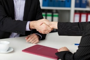 Businesspeople Shaking Hands At Office Desk